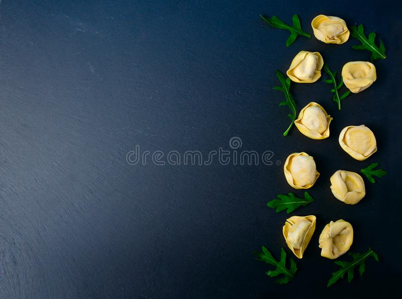Замороженный tortellini на черной предпосылке Итальянский tortellini с свежей рикоттой выходит на черную каменную доску стоковое изображение