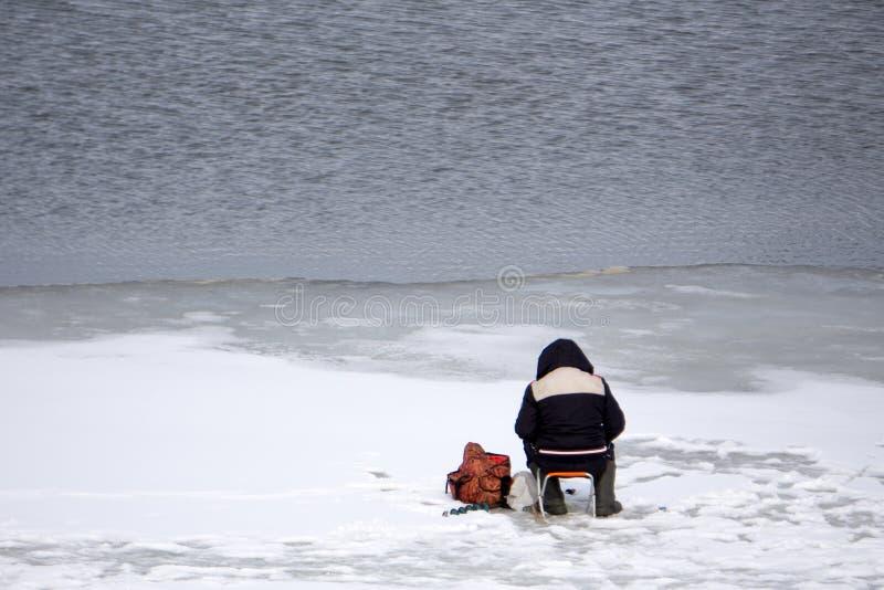 Заморозьте рыболова на мехе лисы озера горы зимы стоковое изображение