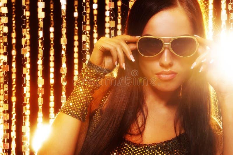 занавесы золотистые над женщиной солнечных очков стоковые изображения