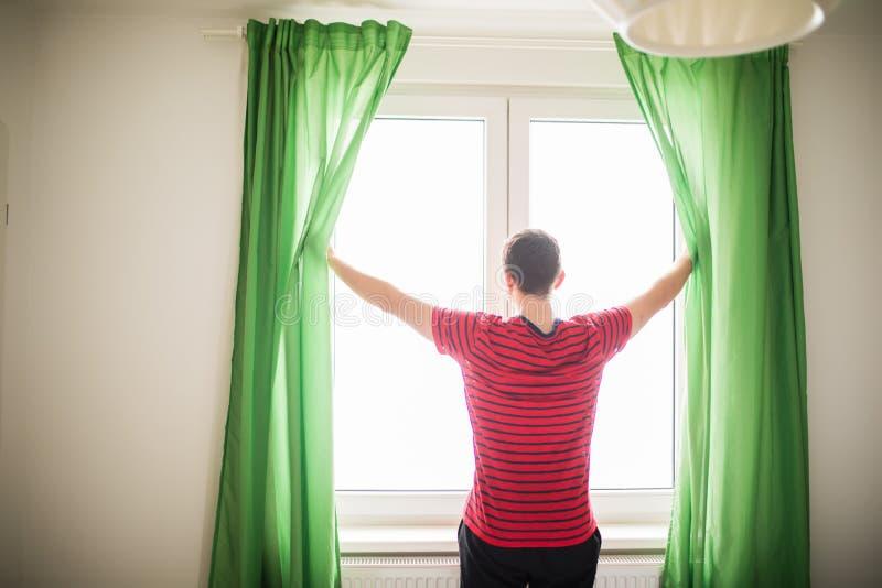 Занавесы отверстия молодого человека в утре и свете, вид сзади, белом стоковое изображение