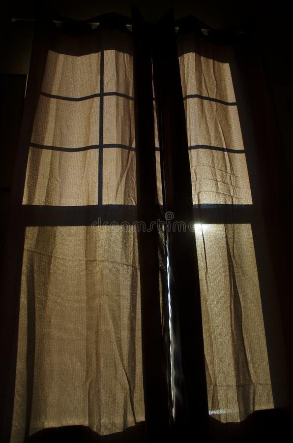 Занавес Брайна при солнечный свет светя через силуэт окна стоковая фотография