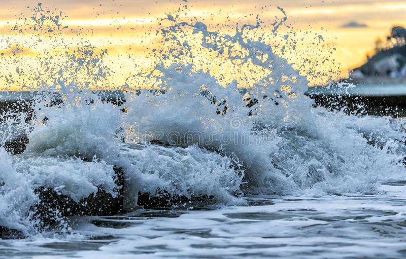 Занимаясь серфингом волна проломы с брызгает и spindrift против выключателя воды во время шторма на побережье Чёрного моря стоковое фото