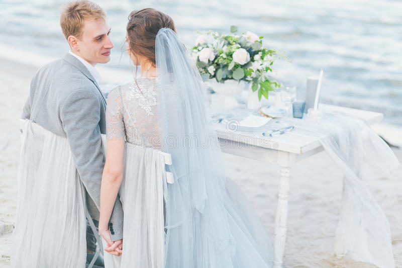 Заново пожененные пары имея обедающий свадьбы морем стоковое фото