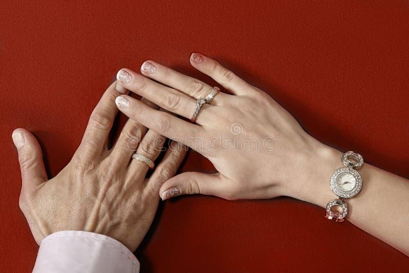 Заново wed руки пары с обручальными кольцами стоковые фото