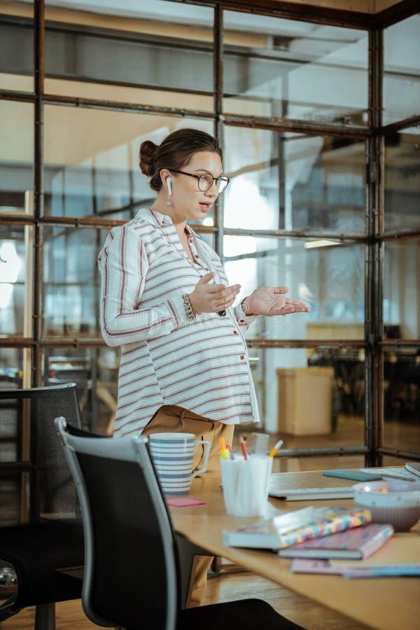 Занятая беременная женщина работая в положении офиса около компьютера стоковые изображения