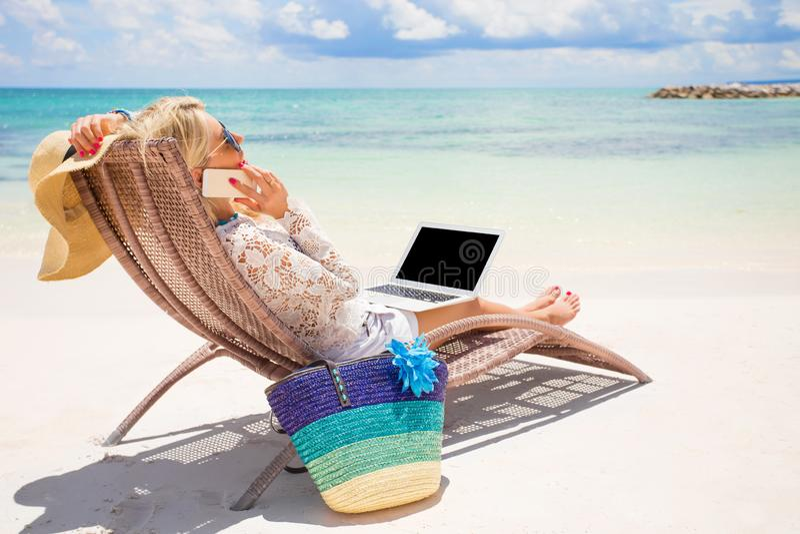 Занятая бизнес-леди работая на пляже стоковое фото