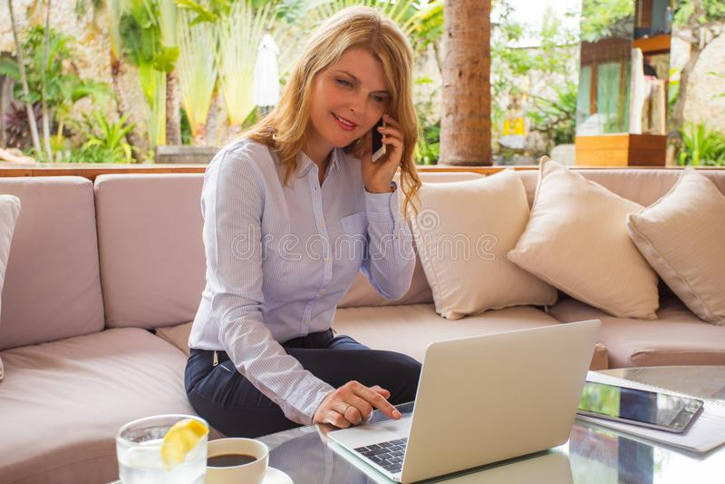 Занятая женщина работая с компьютером и говоря на телефоне стоковая фотография rf