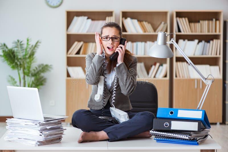 Занятая сердитая коммерсантка сидя на столе в офисе стоковое фото