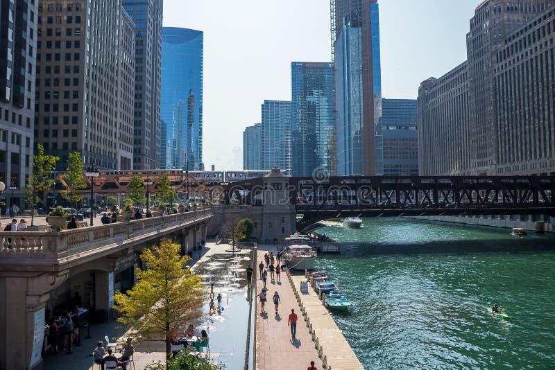 Занятая сцена Чикаго на Реке Чикаго с водой поезда el пересекая, детьми играя на пусковой площадке выплеска, Д-р Wacker регулярны стоковые изображения rf