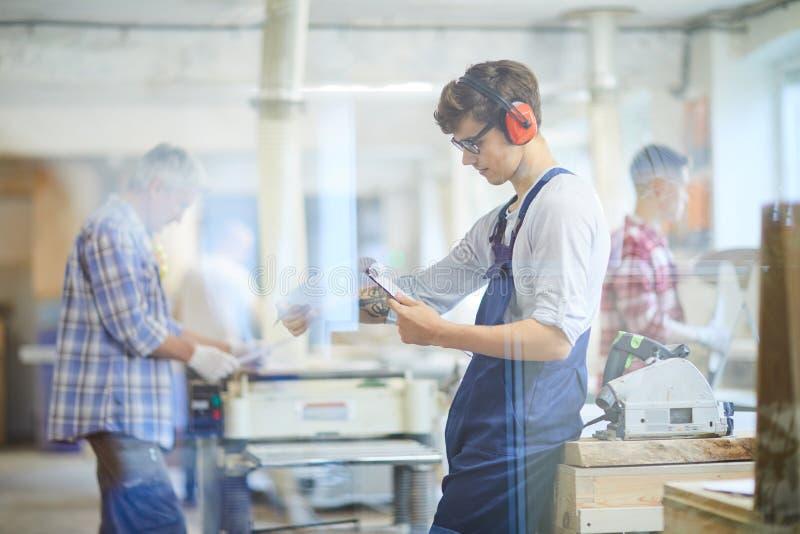 Занятое молодое руководство деятельности чтения плотника в мастерской стоковое изображение rf