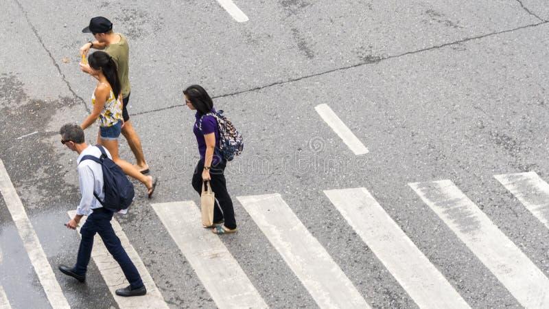 Занятые горожане двигают к пешеходному crosswalk на деле стоковые фото
