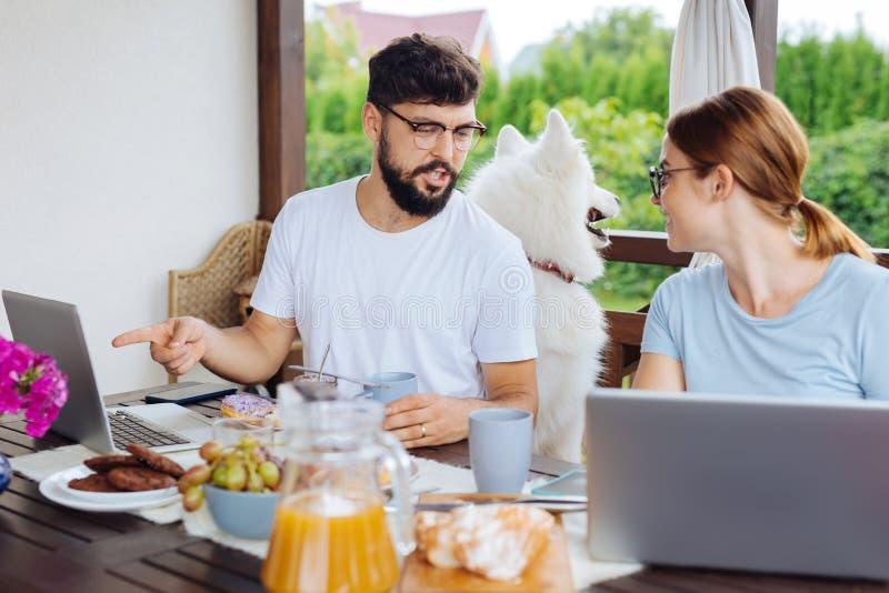 Занятый бородатый предприниматель говоря к его жене имея завтрак стоковые изображения rf