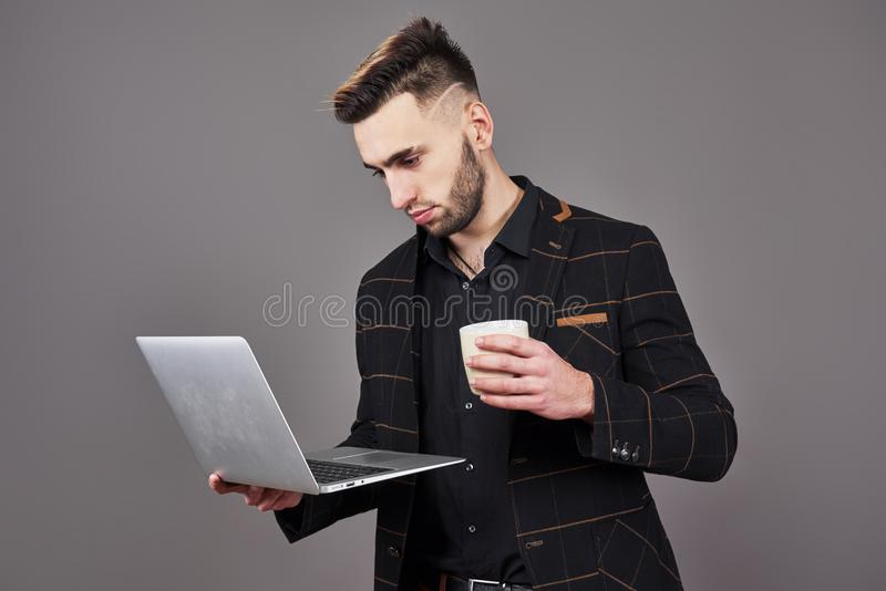 Занятый бородатый человек в деле одевает говорить smartphone и использование портативного компьютера пока держащ чашку кофе в рук стоковые фотографии rf