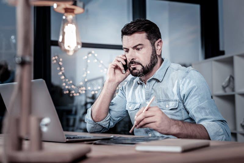 Занятый надежный работник имея телефонный разговор и используя его компьтер-книжку стоковые фотографии rf