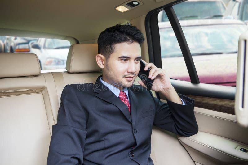 Занятый предприниматель говоря на телефоне в автомобиле стоковое фото