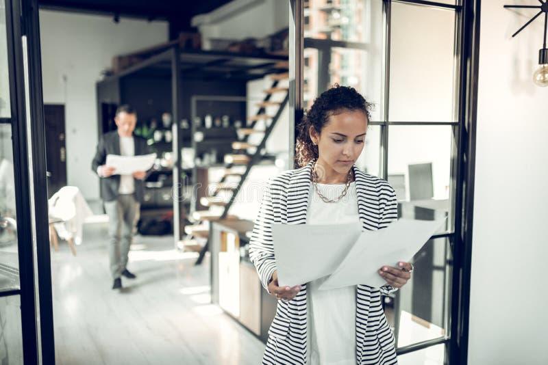 Занятый частный ассистент бизнесмена читая некоторые документы стоковое изображение