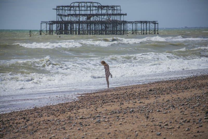 Западная пристань, Брайтон, Англия - охлаждающ на пляже стоковые фотографии rf