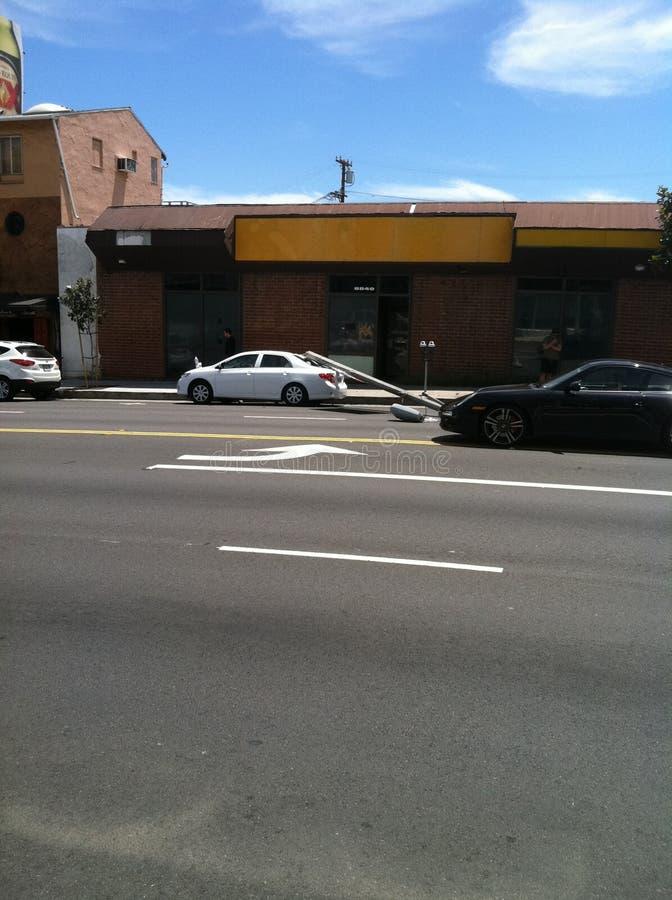 Западный Голливуд, CA/Соединенные Штаты - 6-ое мая 2011: Белый автомобиль ударяет фонарный столб на бульваре захода солнца улицы  стоковые изображения
