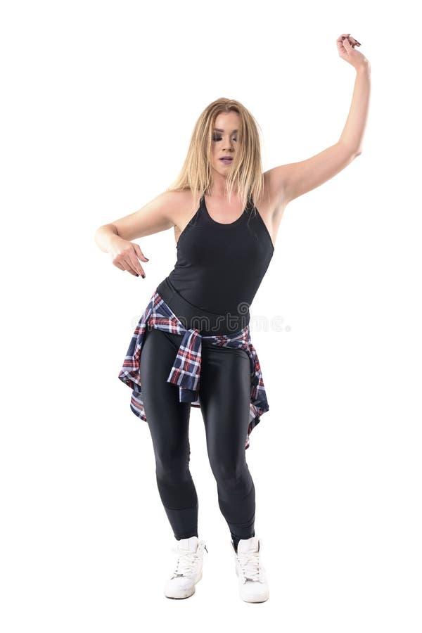 Запальчиво женские танцы инструктора аэробики танца джаза при поднятые оружия пока смотрящ вниз стоковое изображение