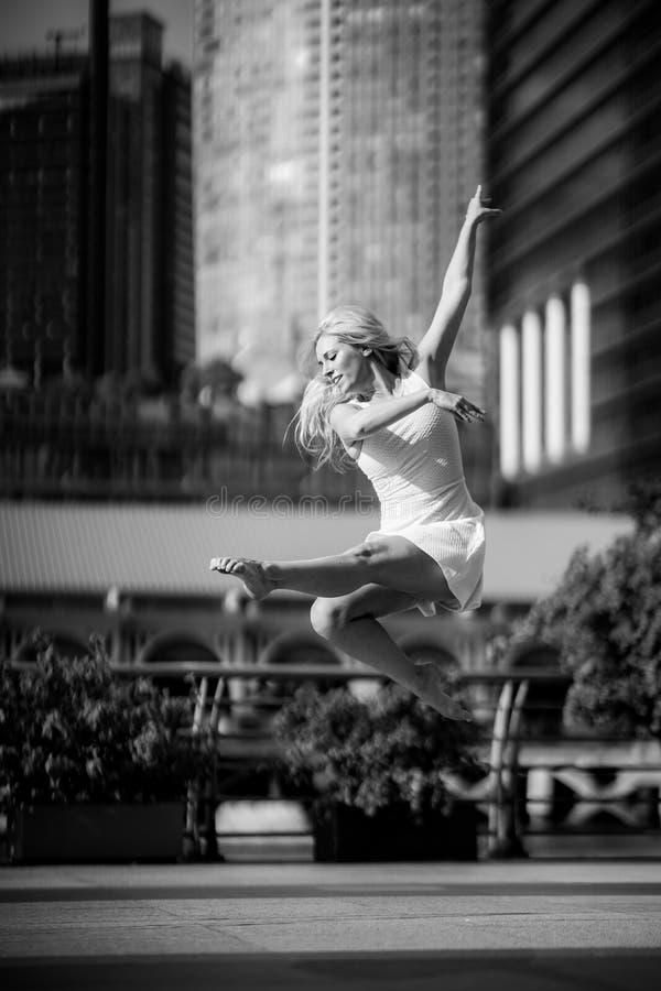 Запальчиво красивый белокурый женский танцор скачет высоко в воздух, стоковое фото