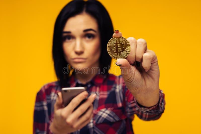 Запачканная женщина держа Bitcoin в ее руке и показывая его стоковое фото rf