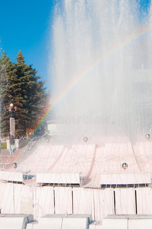 Запачканная красочная радуга на предпосылке брызгать фонтан на солнечный летний день, вертикальную съемку стоковая фотография rf