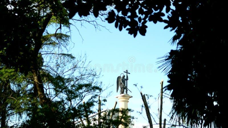 Запачканная статуя силуэта ангела со шпагой против голубого неба в рамке листвы стоковые фотографии rf