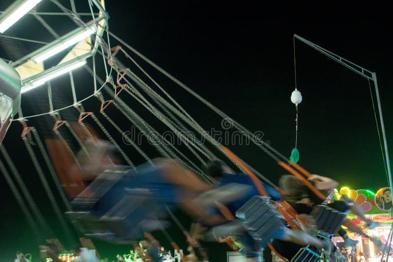 Запачканные места закручивая на Luna Park вечером на юге Италии стоковые фотографии rf