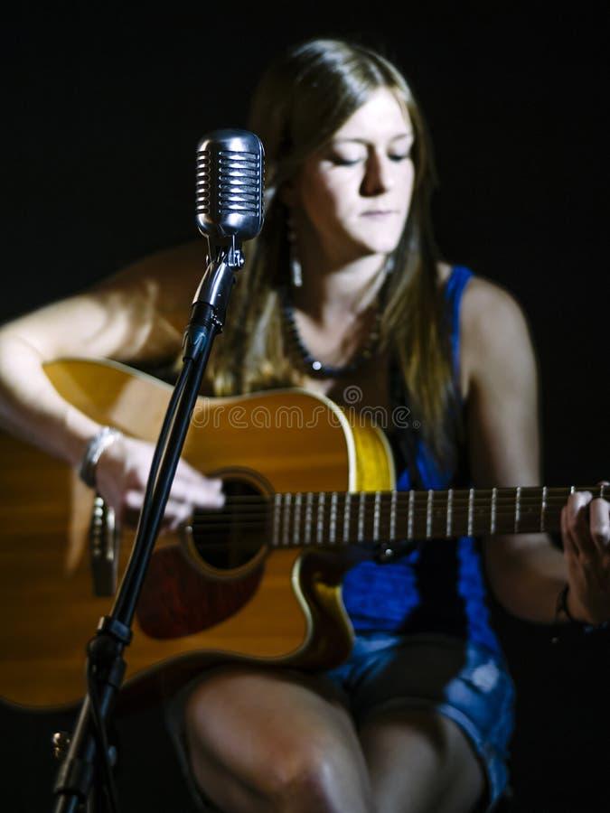 Запачканный гитарист за винтажным микрофоном стоковая фотография rf