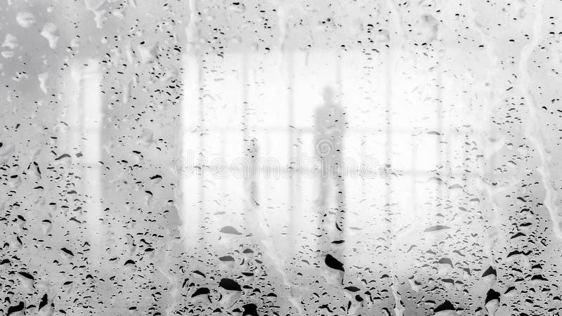 Запачканный силуэт человека в светлой зале через большую влажную стеклянную стену Черно-белое изображение стоковая фотография
