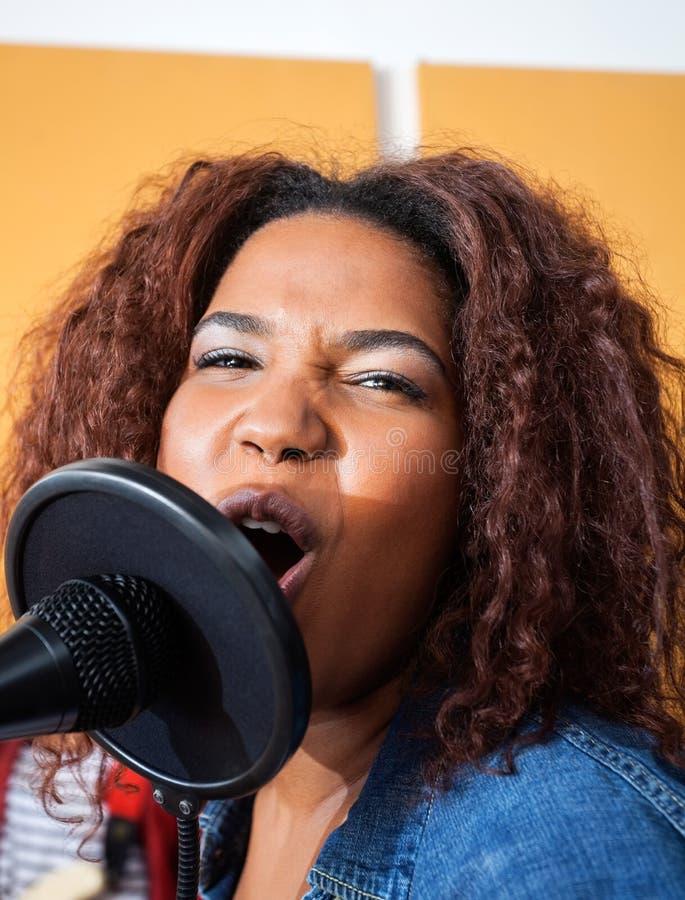 Запальчиво молодая женщина поя в студии звукозаписи стоковое изображение