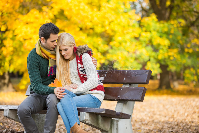 Запальчиво молодой человек обнимая застенчивую женщину на скамейке в парке во время осени стоковая фотография