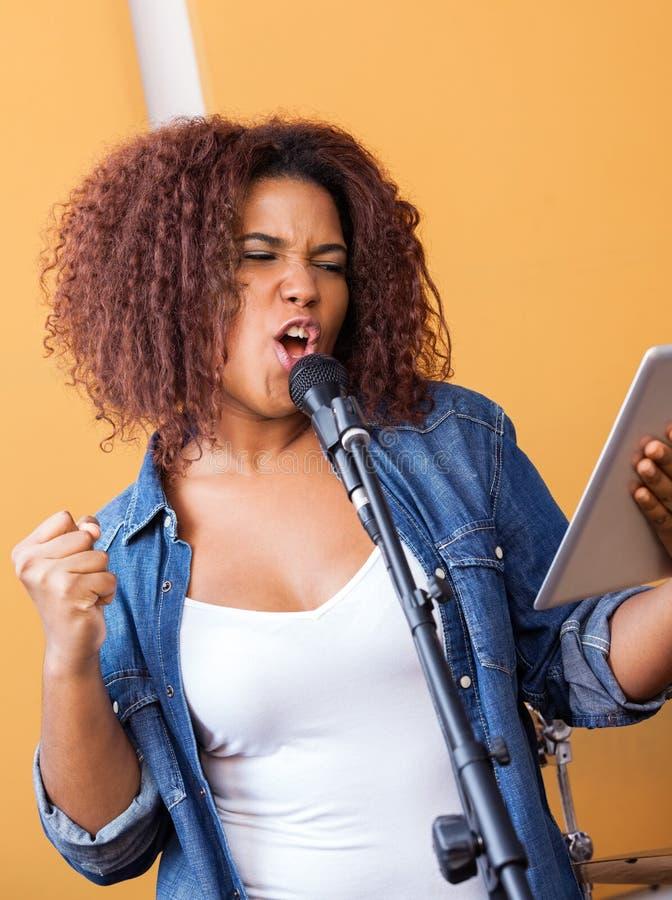 Запальчиво певица держа планшет пока выполняющ стоковое изображение rf