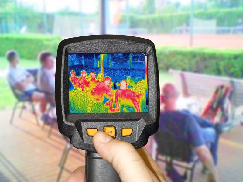 Записывая камера thermovision whit ультракрасная когда люди сидят на таблице стоковое изображение