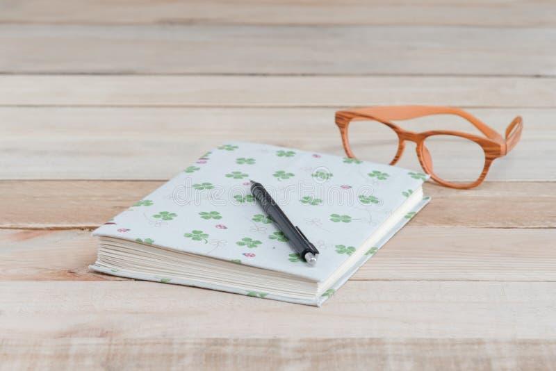 Запишите и ручка, eyeglass на деревянной таблице стоковое фото
