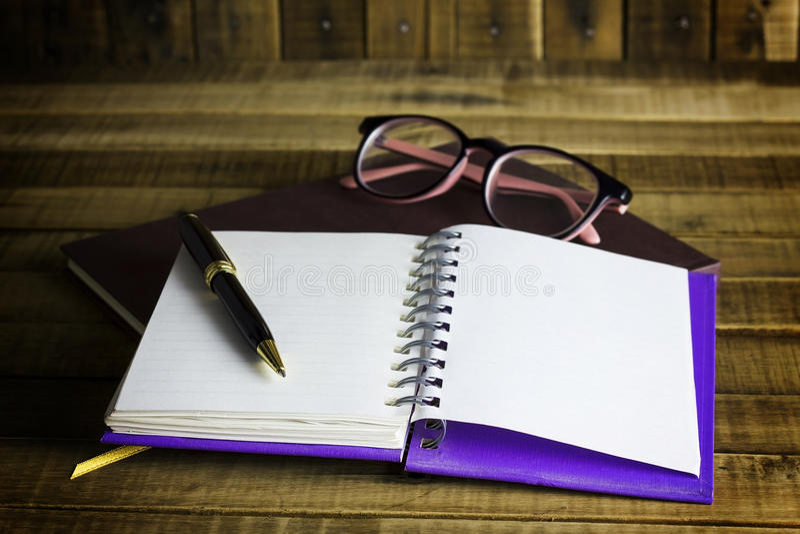 Запишите с стеклами и пишите на деревянной предпосылке стоковое изображение rf