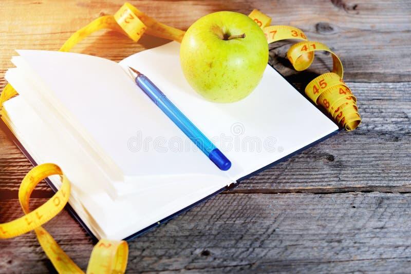 запланирование диетпитания Тетрадь c надпись - диета, измеряя лента, яблоко и ручка стоковое фото rf
