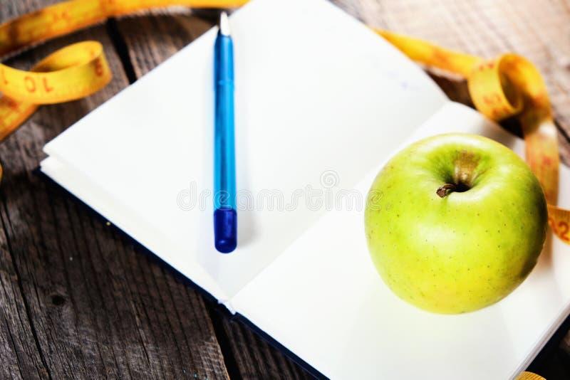 запланирование диетпитания Тетрадь c надпись - диета, измеряя лента, яблоко и ручка стоковые изображения