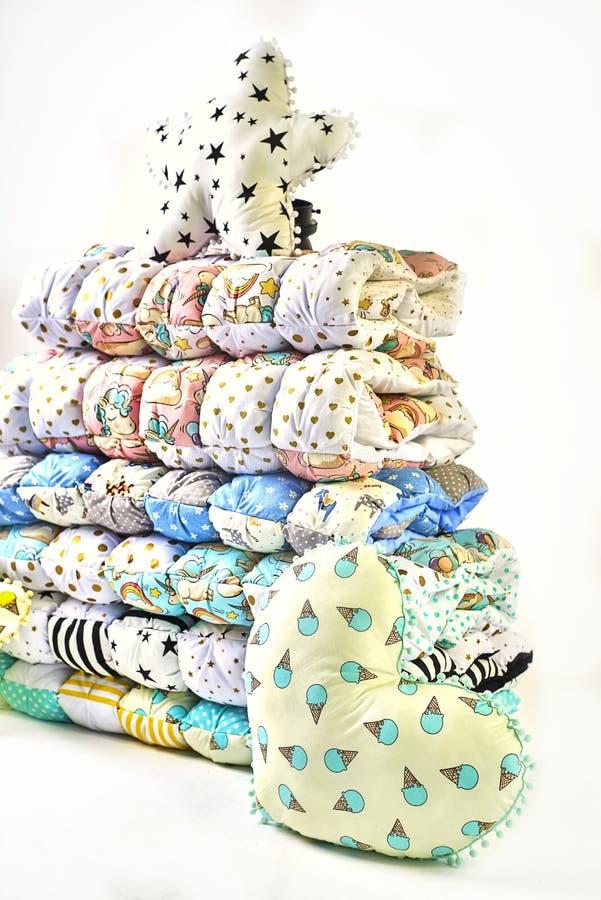 Заплатка и концепция моды - красивый стог красочных лоскутных одеял, покрывал штабелированных в нескольких строк в высоте для хра стоковое изображение