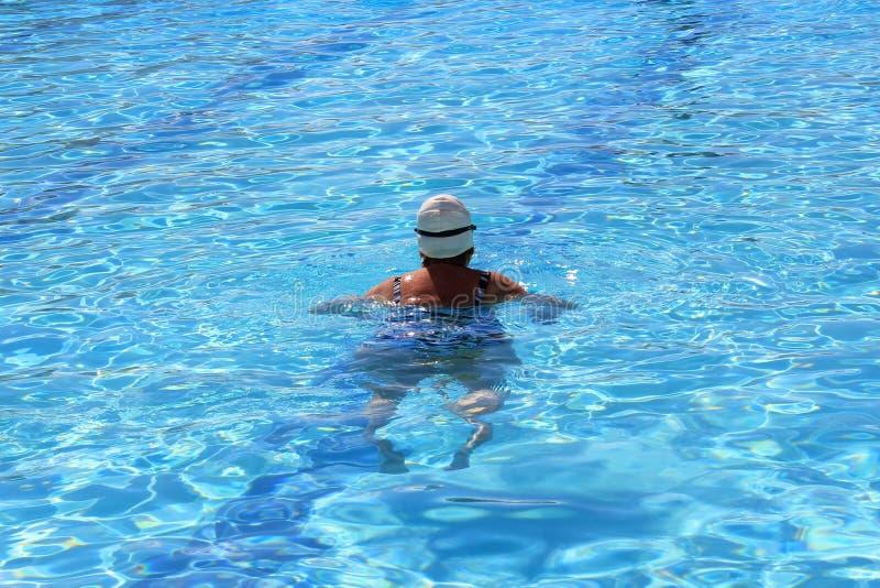 Заплывание женщины в бассейне стоковые изображения