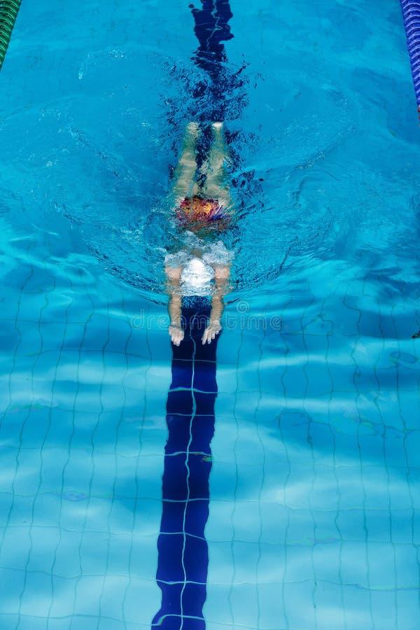 Заплывание женщины с шляпой заплывания в бассейне стоковые фото