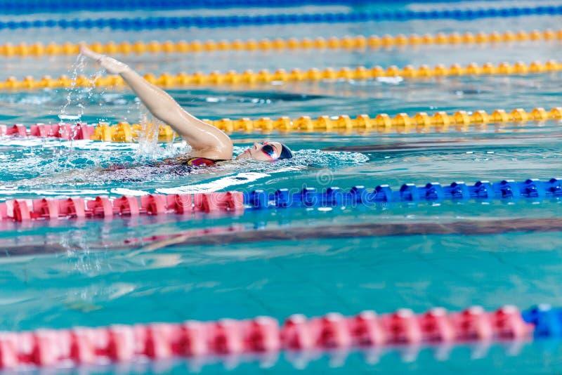 Заплывание женщины с шляпой заплывания в бассейне стоковые изображения rf