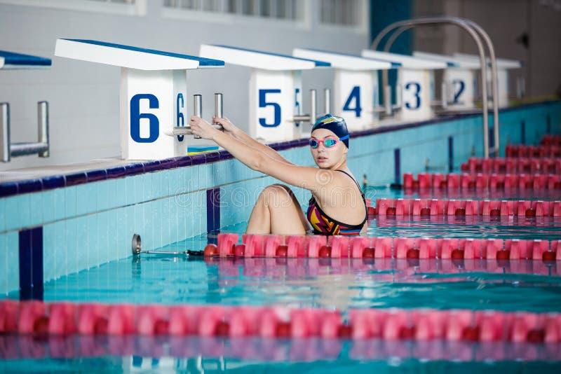 Заплывание женщины с шляпой заплывания в бассейне стоковое изображение rf