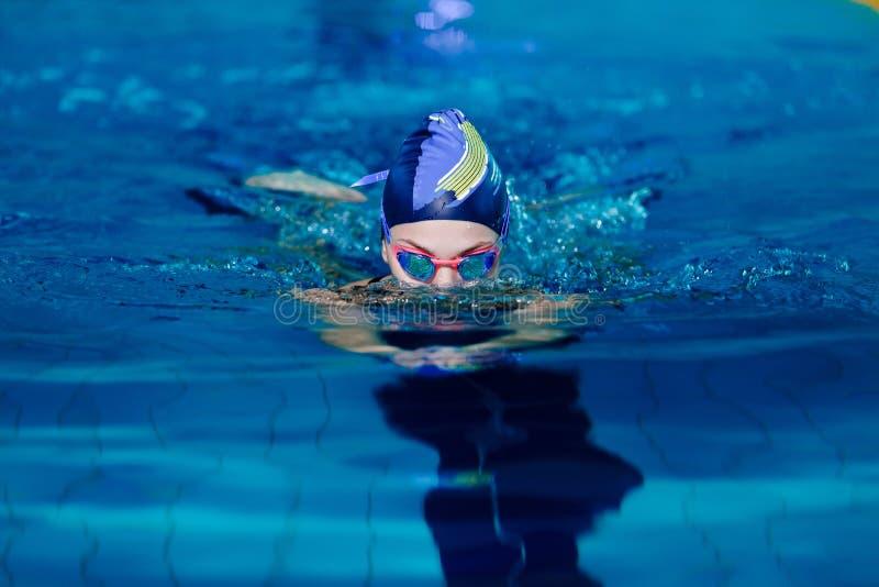 Заплывание женщины с шляпой заплывания в бассейне стоковые фотографии rf