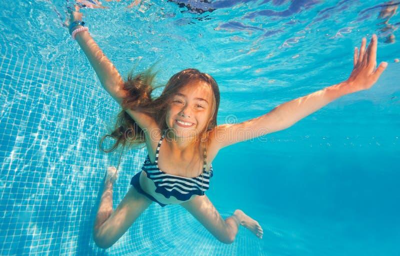 Заплывание и подныривание девушки в голубом бассейне с потехой стоковое фото