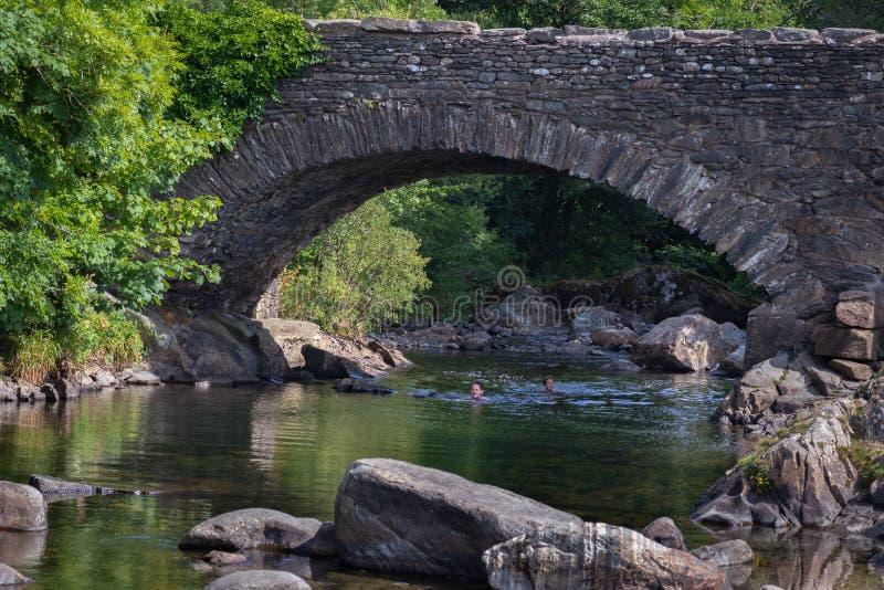 Заплывание отца и дочери в реке Duddon старым каменным br стоковая фотография