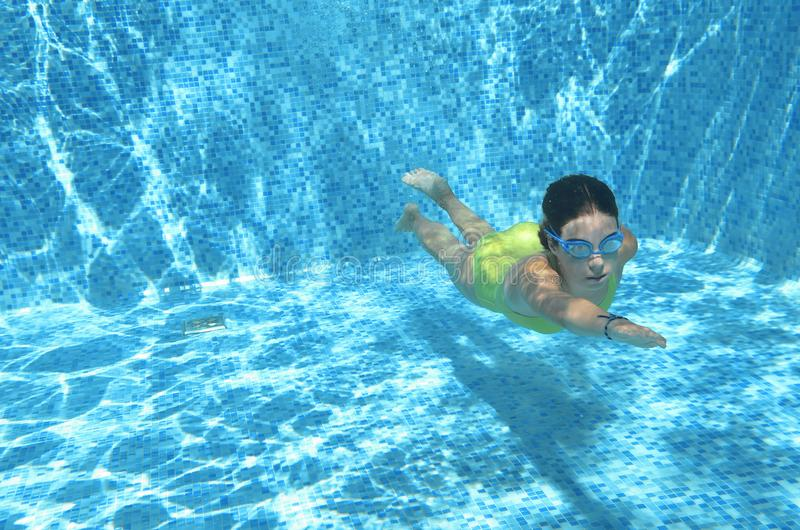 Заплывание пловца маленькой девочки под водой в бассейне и имеет потеху, подросток ныряя под водой, семейный отдых, спорт и фитне стоковые изображения