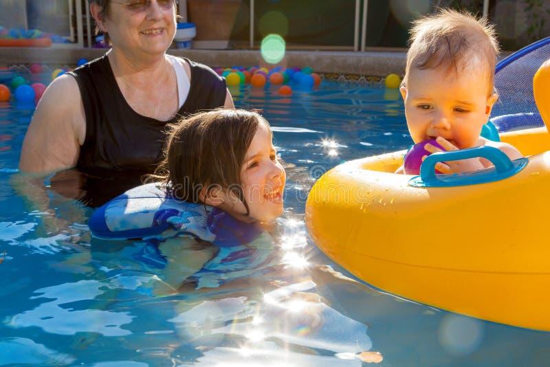 Заплывы бабушки с 2 внуками маленькая девочка усмехаются вверх стоковое фото
