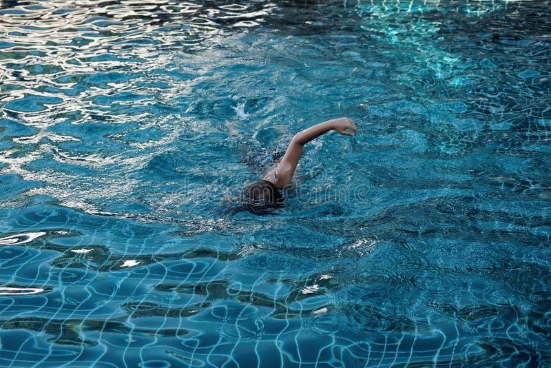Заплывы мальчика в бассейне стоковые фотографии rf