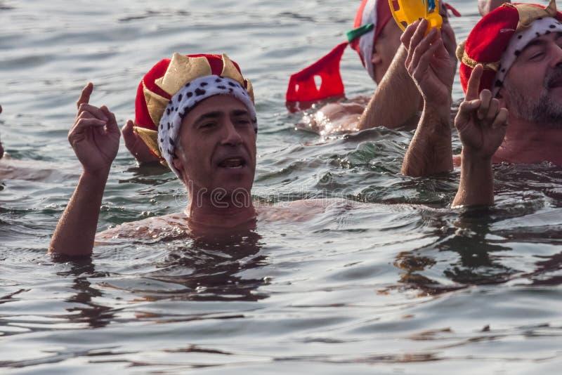 ЗАПЛЫВ 2015 ГАВАНИ РОЖДЕСТВА, БАРСЕЛОНА, порт Vell - 25-ое декабря: Пловцы в костюмах масленицы приветствуют аудиторию стоковые фотографии rf